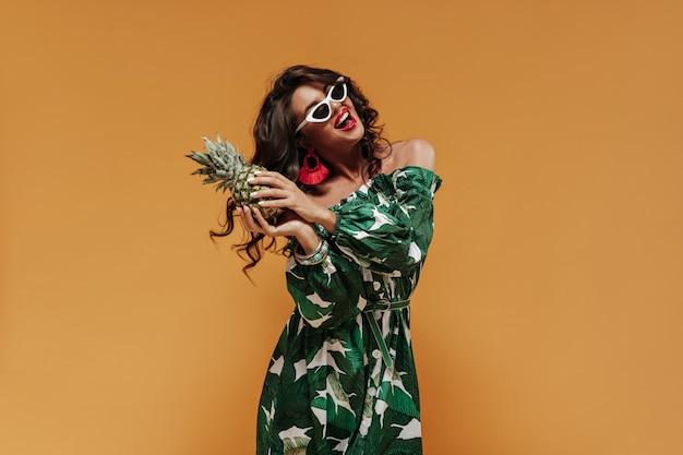 Fröhliche stilvolle frau mit welligem haar und großen lippen in roten ohrringen und bedruckter sommerkleidung, die mit ananas hält und lächelt
