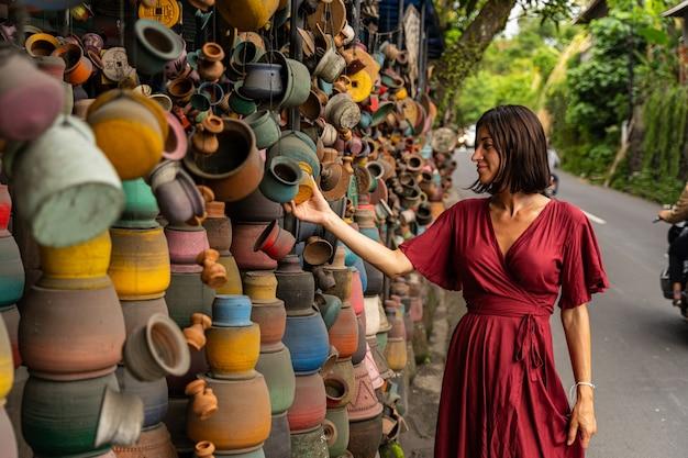 Fröhliche stimmung. freundliche internationale weibliche person, die beim gehen auf dem lokalen markt ein lächeln auf dem gesicht behält