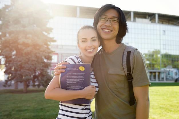 Fröhliche studenten, die draußen stehen