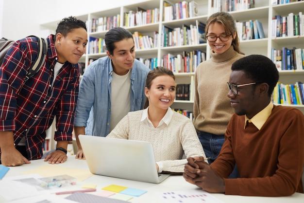 Fröhliche studenten, die in der bibliothek studieren