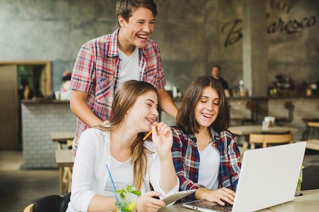 Fröhliche studenten posieren mit laptop