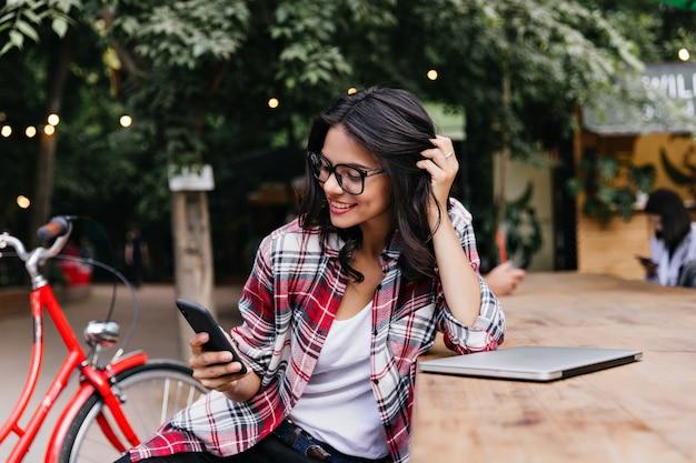 Fröhliche studentin, die mit ihren dunklen haaren spielt. außenporträt des blithesome mädchens, das telefon beim sitzen auf der straße hält.