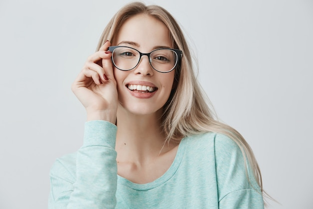 Fröhliche studentin in stilvollen brillen freut sich über erfolgreich bestandene prüfungen und freut sich über ein treffen mit gruppenmitgliedern. erfreute schöne erfreute frau hat attraktiven blick, posiert drinnen.