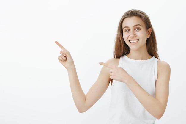 Fröhliche studentin zeigt mit dem finger in die obere linke ecke, zeigt kursbanner und lächelt