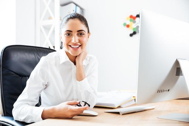 Fröhliche süße geschäftsfrau sitzt am arbeitsplatz mit computer im büro