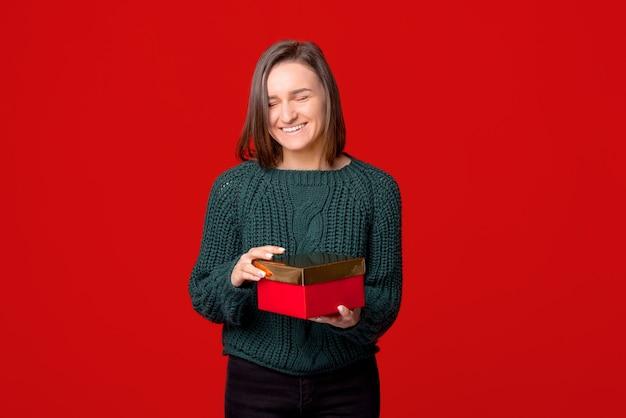Fröhliche süße junge frau, die eine geschenkbox hält, die über rotem lokalisiertem hintergrund steht