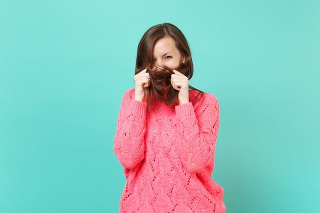 Fröhliche süße junge frau in gestricktem rosa pullover, der das gesicht mit ihrem haar bedeckt, isoliert auf blauem türkis-wandhintergrund-studioporträt. menschen aufrichtige emotionen lifestyle-konzept. kopieren sie platz.