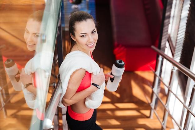 Fröhliche süße junge sportlerin, die im fitnessstudio ein weißes handtuch und eine flasche wasser steht und hält