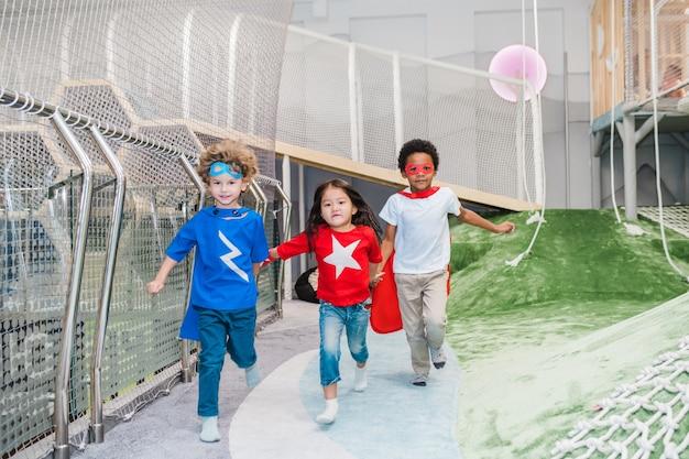 Fröhliche süße kleine kinder der asiatischen, afrikanischen und kaukasischen ethnien, die durch hände halten, während sie entlang spielplatz laufen