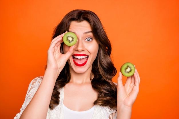 Fröhliche süße nette süße hübsche lockige wellige frau, die aus der hälfte der kiwi schaut und positive gefühle auf gesicht ausdrückt.