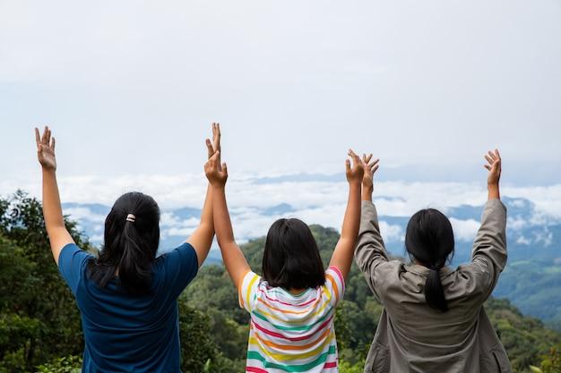 Fröhliche teenager atmen tief frische luft auf dem gipfel des berges ein und atmen saubere luft