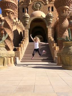 Fröhliche touristen springt in der nähe des tempels