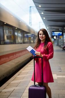 Fröhliche touristenfrau mit großer tasche, reisepass und tickets