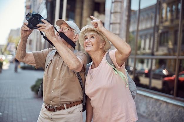 Fröhliche touristin in einem sonnenhut, die mit einem digitalen gerät auf etwas auf ihren ehepartner zeigt