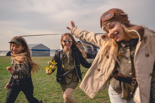 Fröhliche tween-mädchen, die auf dem flugfeld des aeroclubs laufen