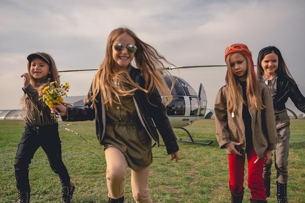 Fröhliche tween-mädchen, die auf dem flugplatz auf dem hintergrund des hubschraubers laufen