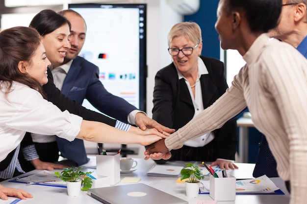 Fröhliche überglückliche geschäftsleute im konferenzraum, die verschiedene kollegen mit neuer gelegenheit zum siegtreffen im broadroom-büro feiern.