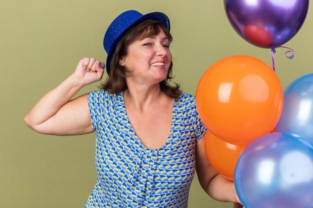 Fröhliche und aufgeregte frau mittleren alters in partyhut mit einem haufen bunter luftballons, die spaß haben, fröhlich lächelnd die geburtstagsfeier zu feiern, die über grüner wand steht