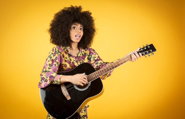 Fröhliche und beliebte hübsche frau mit afro-haaren, die gitarre spielen, isoliert