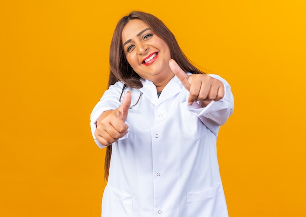 Fröhliche und fröhliche ärztin mittleren alters im weißen kittel mit stethoskop, die lächelnd mit daumen nach oben aussieht
