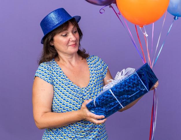 Fröhliche und fröhliche frau mittleren alters mit partyhut, die einen haufen bunter luftballons hält und sie mit einem lächeln betrachtet, das die geburtstagsfeier über der lila wand feiert
