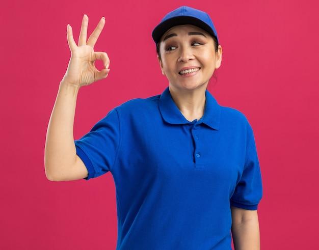 Fröhliche und fröhliche junge lieferfrau in blauer uniform und mütze, die lächelt und dabei ein gutes zeichen macht