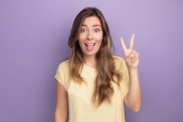 Fröhliche und fröhliche junge schöne frau in beigem t-shirt mit blick auf die kamera, die die zunge herausstreckt und das v-zeichen auf violettem hintergrund zeigt