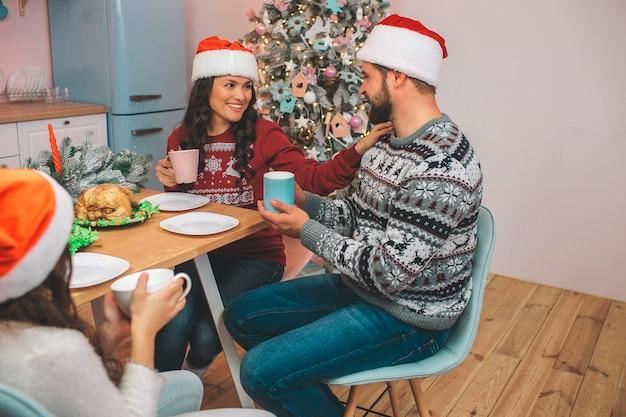 Fröhliche und glückliche junge frau sitzt am tisch mit ehemann und tochter. sie sieht ihn an und berührt seine schulter. guy sieht sie an. sie halten tassen in händen. die leute tragen rote hüte.