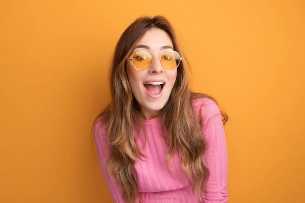 Fröhliche und glückliche junge schöne frau in rosa top mit brille und blick in die kamera lächelnd stehend über orangem hintergrund