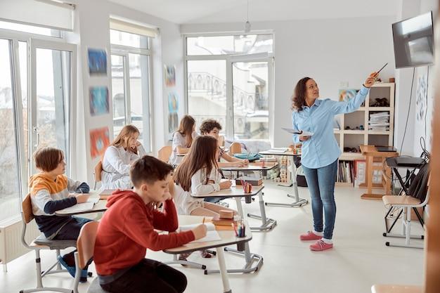 Fröhliche und glückliche kinder, die am schreibtisch sitzen, während lehrer im klassenzimmer sprechen. grundschulkinder sitzen auf schreibtischen.