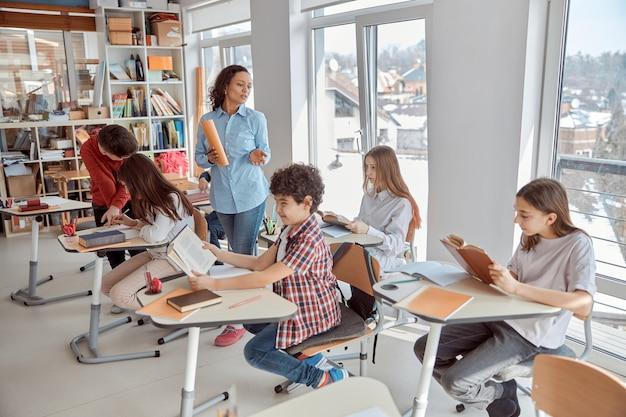 Fröhliche und glückliche kinder, die am schreibtisch sitzen, während lehrer im klassenzimmer sprechen.