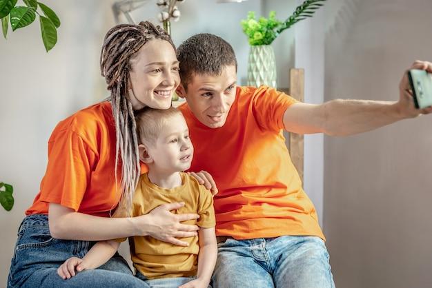 Fröhliche und lustige papa mama und kind machen fotos auf einem handy