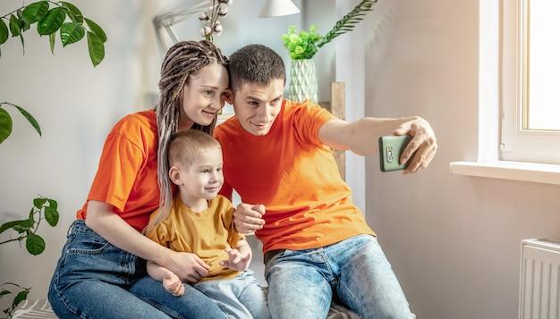 Fröhliche und lustige papa-mutter und kind machen fotos mit einer handykamera zu hause