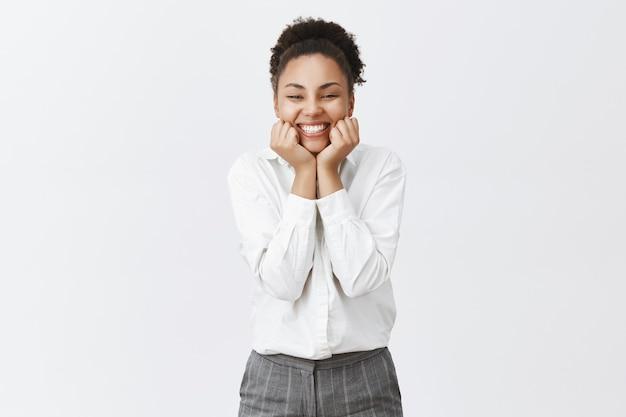 Fröhliche und niedliche afroamerikanische büroangestellte, die entzückt aussieht und amüsiert lächelt