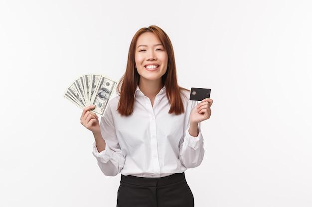 Fröhliche und zufriedene erfolgreiche geschäftsfrau verdienen geld mit harter arbeit, halten bargeld mit kreditkarte, strahlendes lächeln erfreut, einkaufen, bereit für teure urlaubstour,
