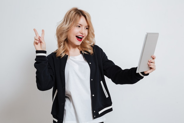 Fröhliche verspielte junge frau, die tablet-computer hält und friedensgeste zeigt