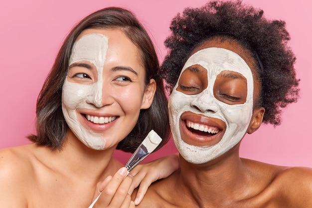 Fröhliche, vielfältige frauen tragen gesichtsmasken mit kosmetischem bürstenlächeln auf und zeigen weiße zähne, die sich eng um haut und körper kümmern, die über rosafarbener wand isoliert sind.