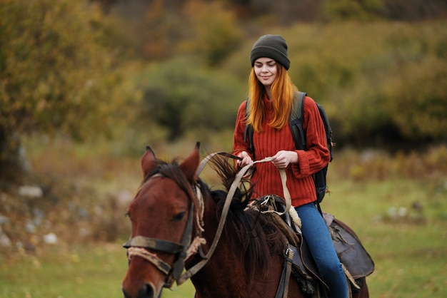 Fröhliche wandererin reiten auf einem pferdespaß in die berge