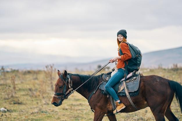 Fröhliche wanderin, die ein pferd in den bergen reitet, reisen