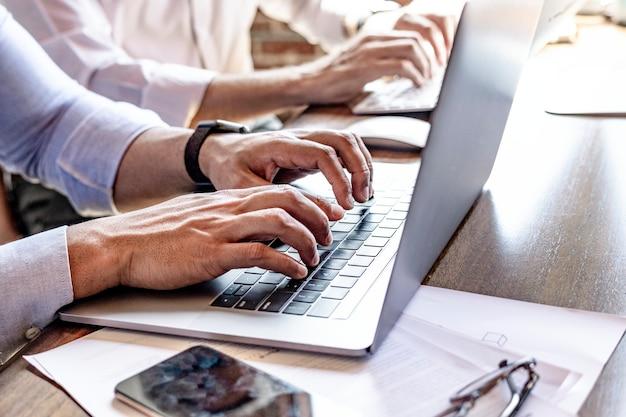 Fröhliche webentwickler, die an einem laptop arbeiten