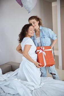 Fröhliche weibliche person, die positivität ausdrückt, während sie eine große geschenkbox hält