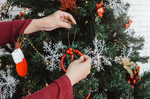 Fröhliche weihnachten. hand der jungen frau in der roten strickjacke zu hause verzierend auf schönem weihnachten