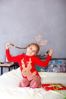 Fröhliche weihnachten. neujahr. kleines mädchen mit zöpfen auf ihrem kopf mit weihnachtsgeschenkbox zu hause. kind im roten schlafanzug und mit hirschhörnern auf dem kopf am heiligen abend hat spaß und öffnet geschenk. winter