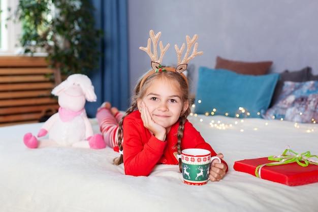Fröhliche weihnachten. neujahr. kleines mädchen mit zöpfen auf kopf mit weihnachtsgeschenkbox zu hause. fröhliches kind im roten schlafanzug und mit hirschhörnern auf dem kopf am heiligabend trinkt milch und öffnet geschenk.