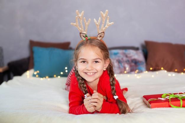 Fröhliche weihnachten. neujahr. porträt des kleinen lächelnden mädchens mit weihnachtsgeschenkbox zu hause. fröhliches kind im roten schlafanzug und mit hirschhörnern auf dem kopf am heiligabend liegt auf dem bett und öffnet geschenk.