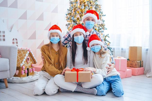Fröhliche weihnachten. vierköpfige familie mit geschenken an weihnachten. eltern und kinder tragen gesichtsmasken