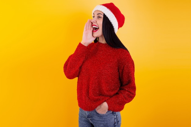 Fröhliche weihnachtsfrau aufgeregt sagen hallo auf gelbem hintergrund mit roter weihnachtsmütze, schreit rabatte und hält seine hand um den mund. weihnachtsrabatt inhalt.