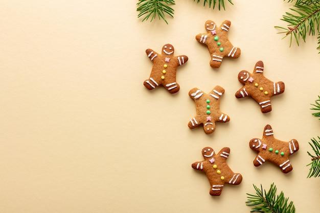 Fröhliche weihnachtslebkuchenmänner mit fichtenzweigen auf gelb