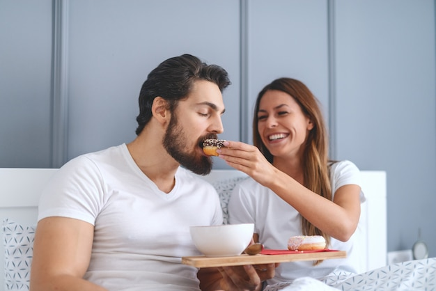 Fröhliche wunderschöne kaukasische brünette, die morgens im bett sitzt und ihren mann mit donut füttert.