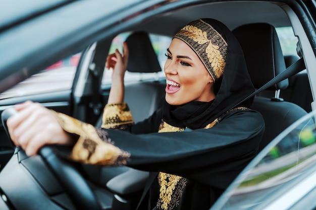 Fröhliche wunderschöne positive muslimische frau in traditioneller kleidung, die ihr neues auto fährt, musik hört und singt.
